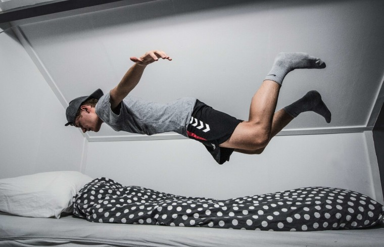 Man jumping into bed mid-air